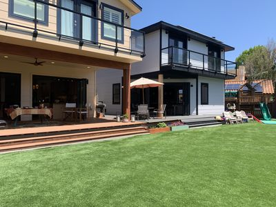 Backyard view of both houses, connected by expansive turf and deck