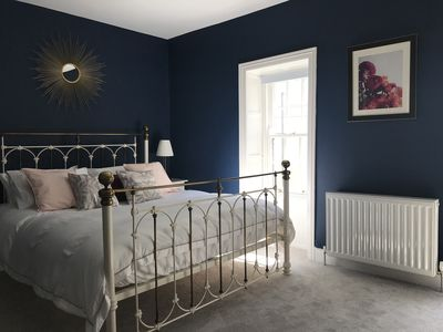 Master bedroom features Laura Ashley super-king bed and midnight blue colour