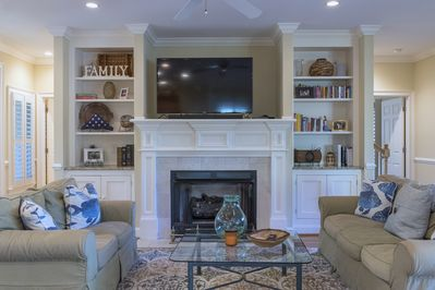 The living room has a large flat screen TV, fireplace and cozy sofas.