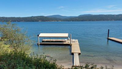 Covered private dock, chaise lounges, and sandy beach.