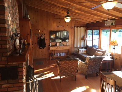 Living room with large windows with view of the river and cozy fireplace.