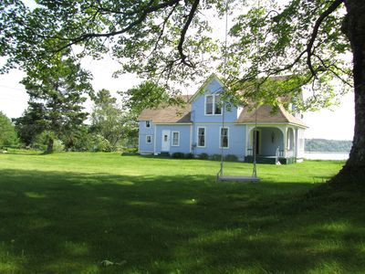 The front of the house with a swing in the maple tree and a front sitting porch.