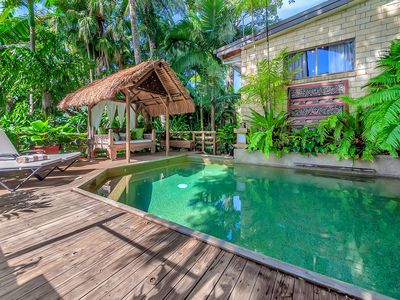 Bali style pool area with sunloungers and beautiful daybed in the thatched hut.
