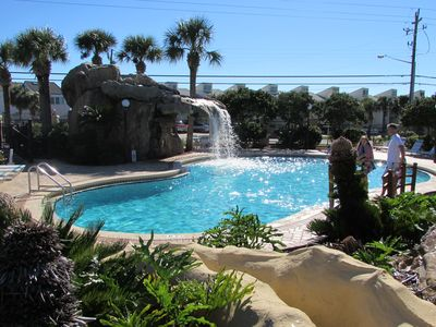 Front pool with waterfall and lots of palm trees, landscaping.