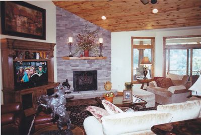Great Room, stone fireplace, TV, solid walnut floor, all glass to view deck