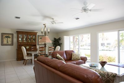 Living room with leather couches and TV armoire and clear views of the water.