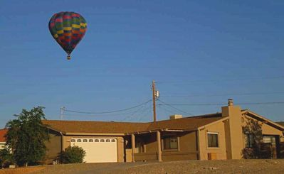 Front of home with hot air balloon sailing above