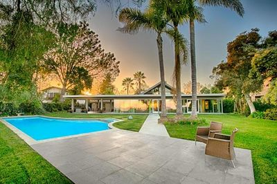 The peaceful back yard of this home has a large lawn,patio swimming pool. Diving board has been removed.