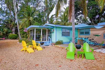 The Ibis cottage exterior featuring adirondack chairs, barbecue and private lanai.