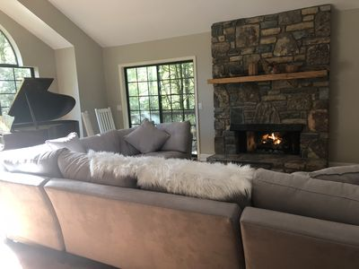 soaring ceilings, a baby grand piano and a cozy fire