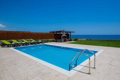 Private pool, terrace, and lawn with panoramic sea views