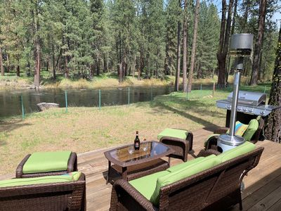 Relax on the back deck with a view of the river and forest.