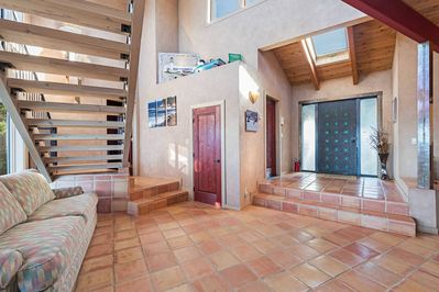 Entryway with earth tone tile and staircase