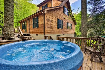 The 2-bedroom, 2-bath cabin boasts a hot tub, creek views, 1.7-acre yard & more!