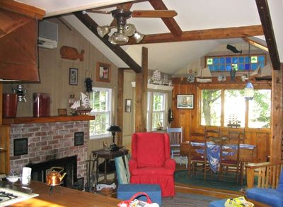 Living /Dining room with wood-burning fireplace, cathedral ceiling & fan