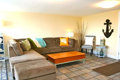 Large sectional in the living room, and single chair.