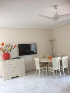 Lounge with 50inch wall mounted TV and dining table and cabinet