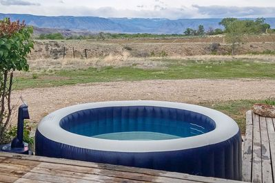 Soak in the hot tub with mountain views in the distance.