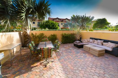 Beautiful back patio with gas grill, couch and table