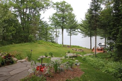 View of backyard, lake, deck and firepit