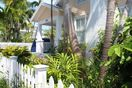 Front of Home Features Lush Tropical Landscape & Additional Parking.