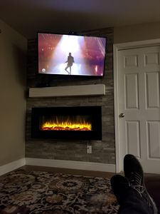 Feature Wall with electric fireplace and wall-mounted television in living room.