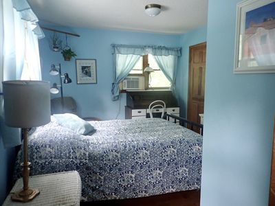 Double bed, La-Z-Boy recliner, writing desk, and two windows overlooking farm