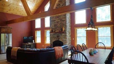 cathedral ceiling in living room with large beams. 30 FT stone wood fireplace.