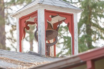 Ring the dinner bell which rest on top of the roof from handle located on porch