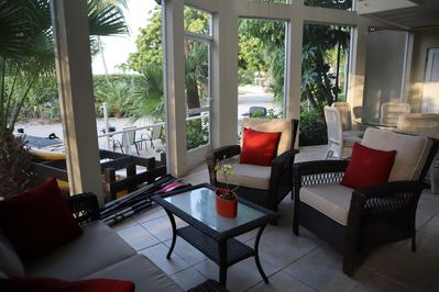Outdoor living and dining areas on screened in lanai facing gardens and bay.
