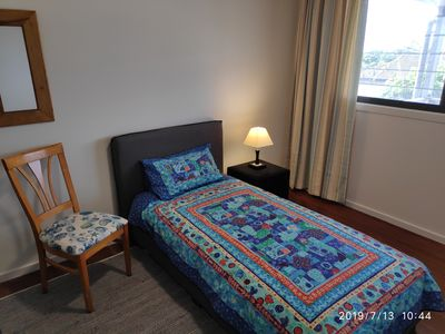 Third bedroom with single bed and windows onto deck.