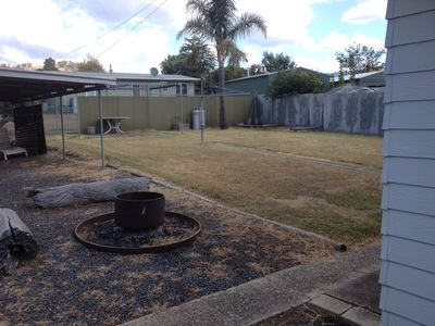 Spacious backyard with fire pit and clothes line.
