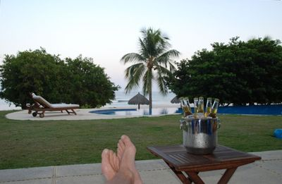 Relaxing on our private patio next to the pool and steps to ocean.