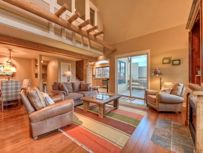 Another view of living room with log accents, hardwood floors, and fireplace.