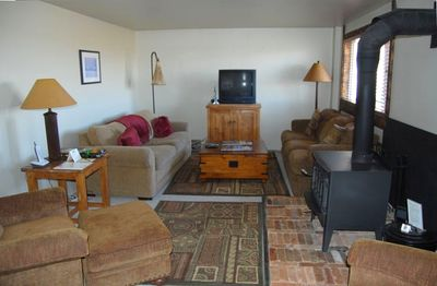 Living room, woodstove, pull-out couch, TV and stereo/DVD, views out windows