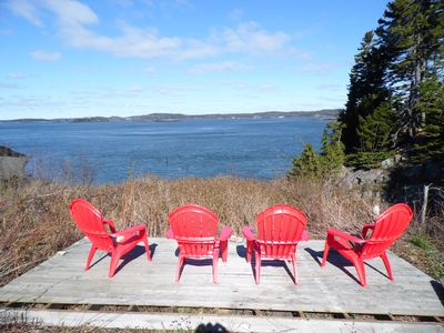 Adirondack chairs on deck overlooking the ocean.