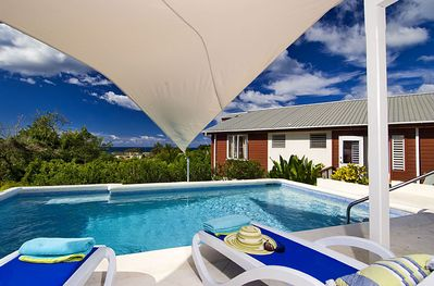 Deck chairs next to pool with canvas sail to block the sun