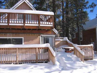 Winter View of back of home with decks and Hot tub.