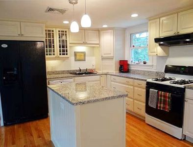 Kitchen with large refrigerator, gas stove and dishwasher.