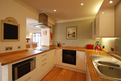 Modern equipped kitchen with Bosh appliances and induction hob.