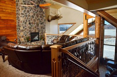Upstairs sitting area with gas fireplace, massage chair and lake view.