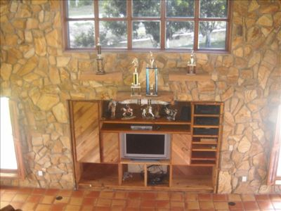 Built-in entertainment center amidst fieldstone wall; windows border both sides