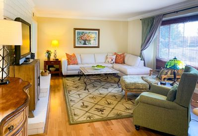 Luxurious, spacious, comfortable living room, designer furnishings, wood floors.