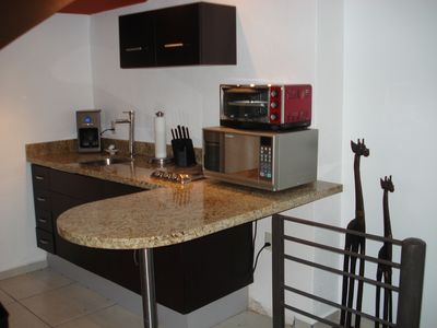 Kitchenette with fridge, microwave, mixer, coffee maker, little grill…