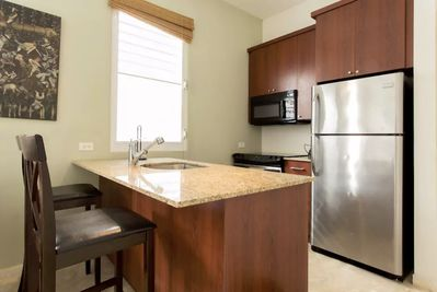 Fully equipped kitchen with oven, stove, microwave, coffee maker and utensils