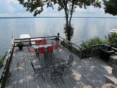 Boat house deck with gas grill and two patio tables.
