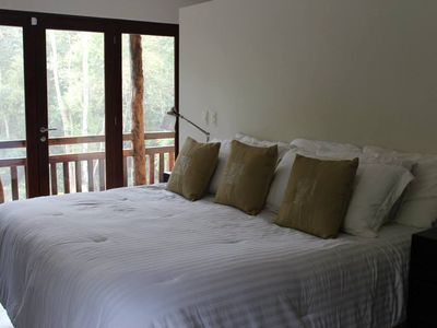 Bedroom with king bed, balcony overlooking pool and jungle, flat screen TV, A/C
