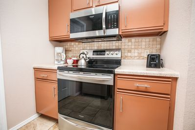 Kitchen w/ microwave, stove, fridge with ice maker, & dishwasher with detergen