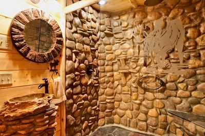 """Elegant bathroom in the """"Wolf Room"""" with a large rock shower and glass doors"""