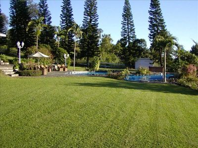 Hhouse and pools are surrounded by green lawns and tropical flora